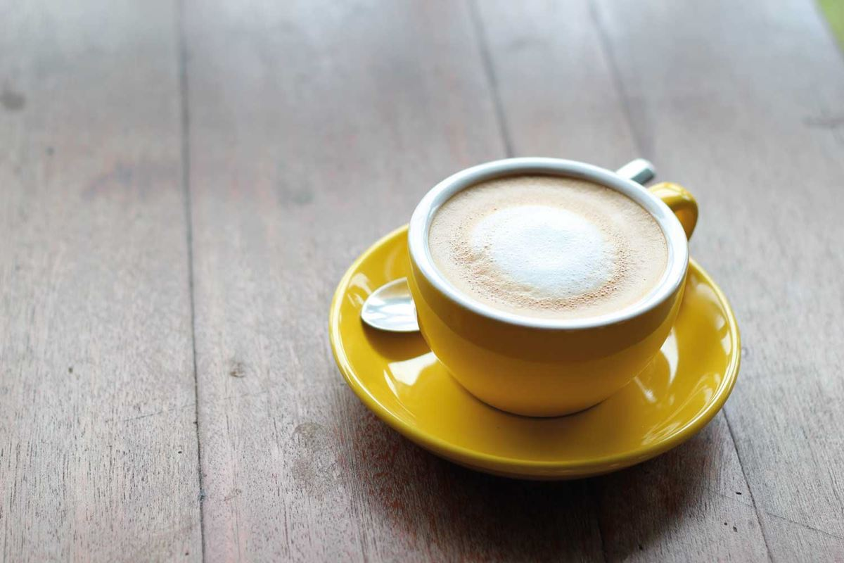 A latte coffee in a yellow mug on a saucer