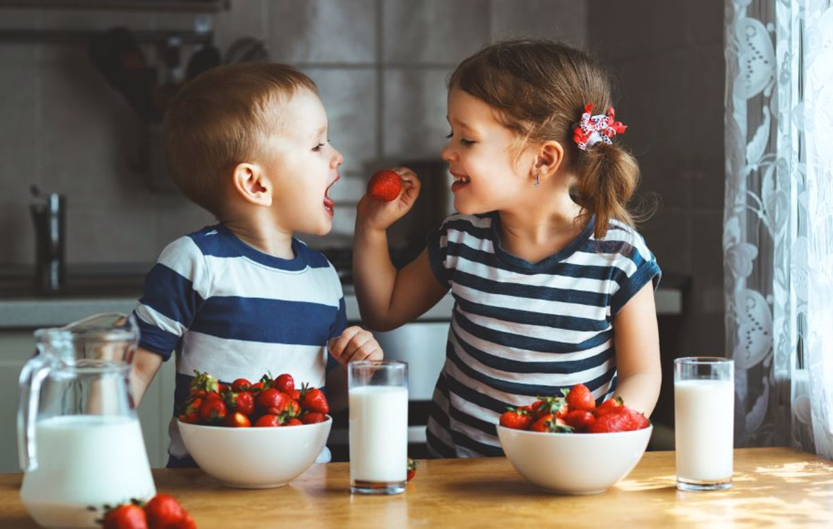 Brother and sister enjoying strawberries