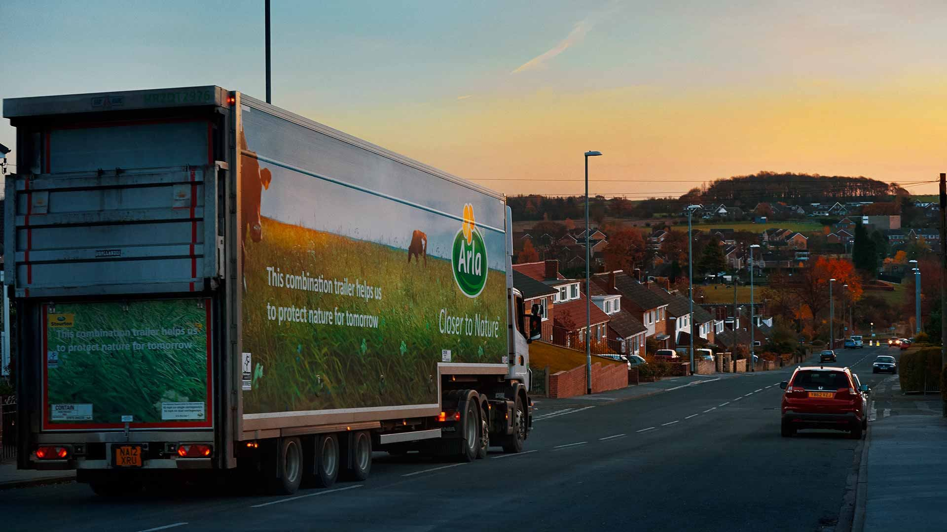 Arla trailer truck driving through a residential area at sunset