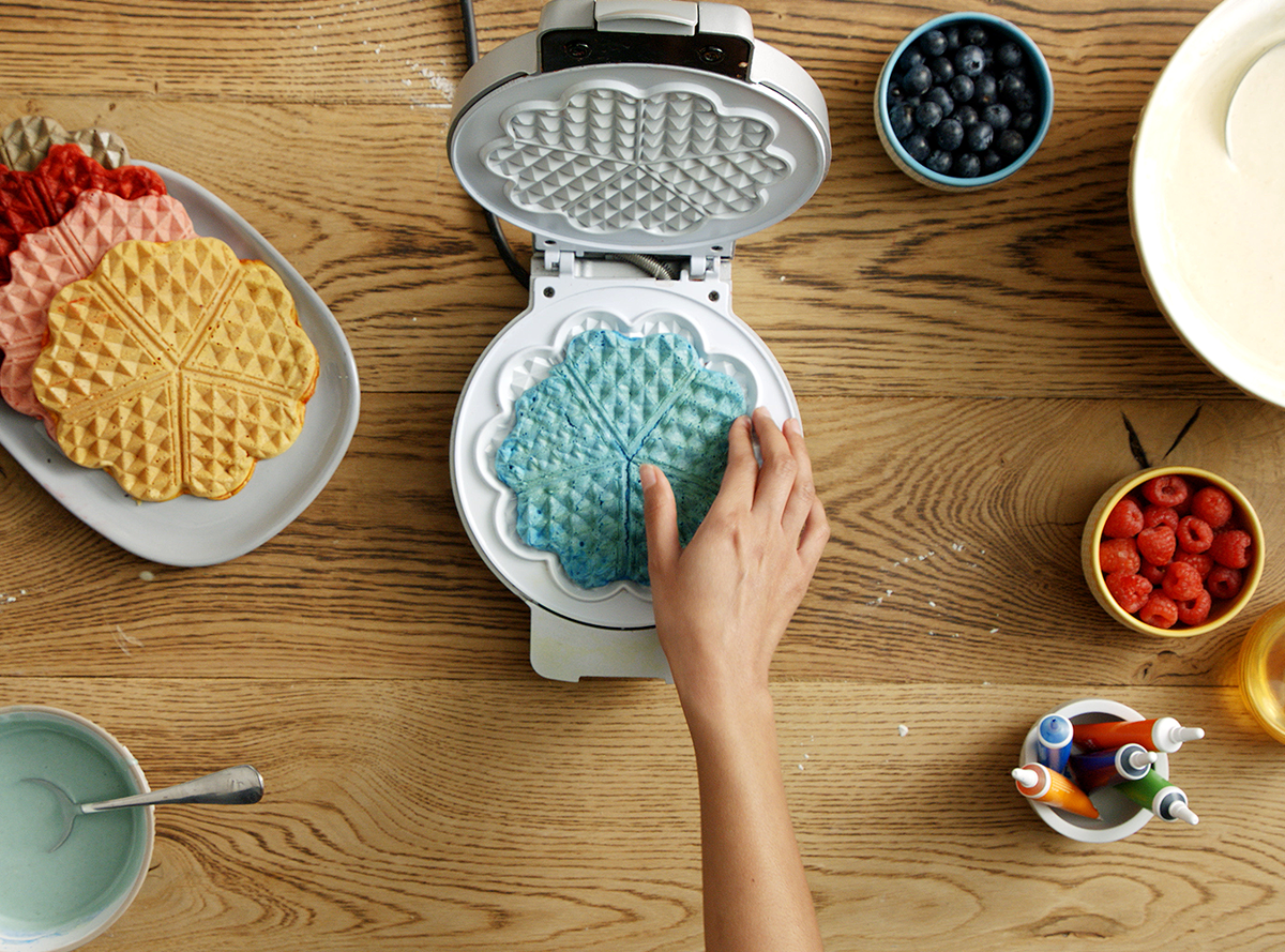 A hand removing a blue waffle from a waffle maker