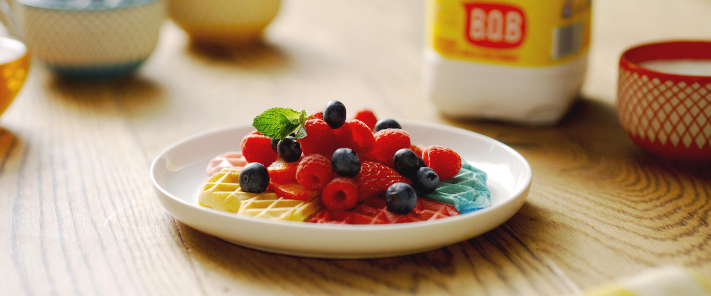 Rainbow waffles topped with berries and mint