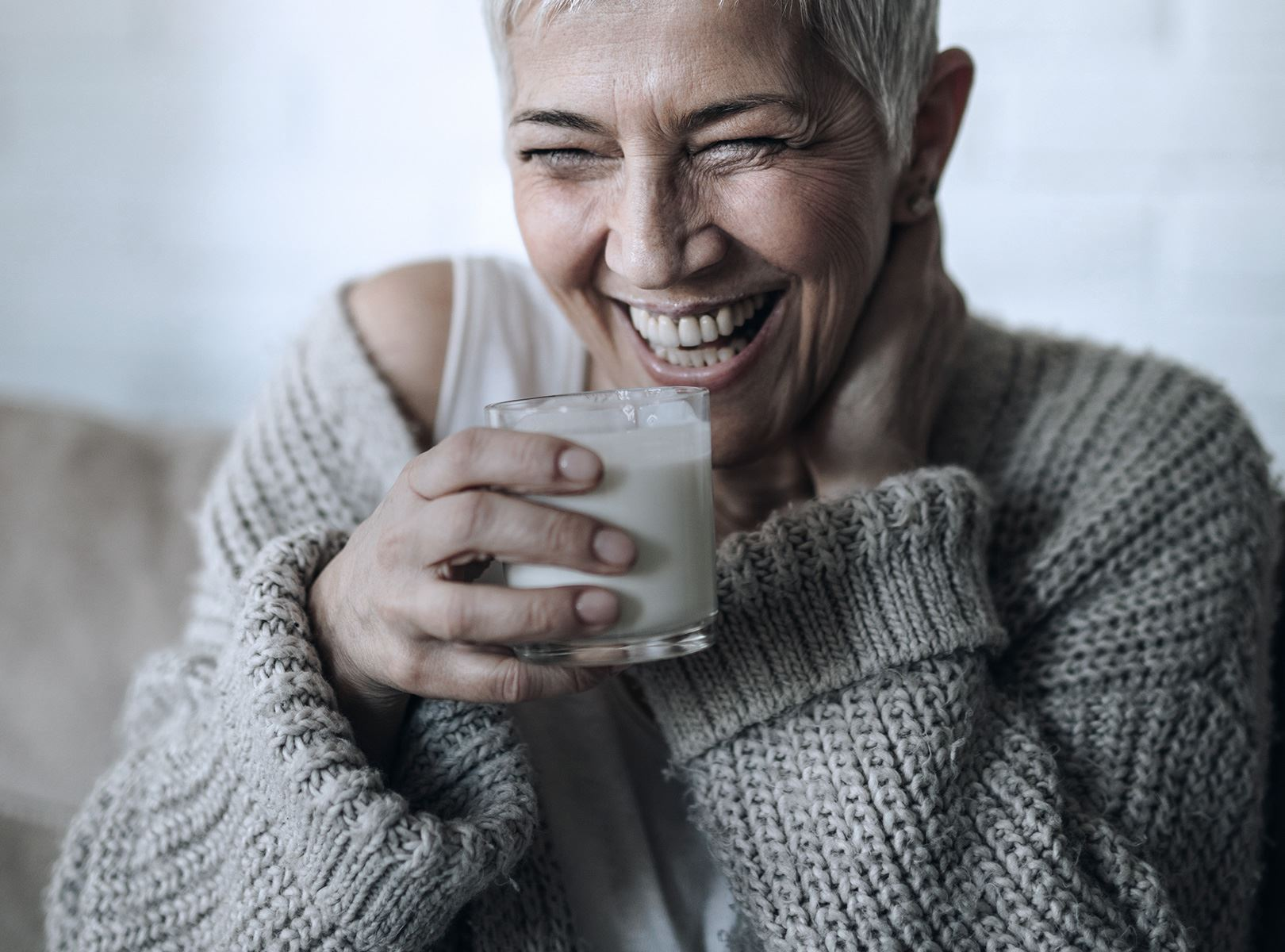 A woman laughing with a glass of milk in her hand