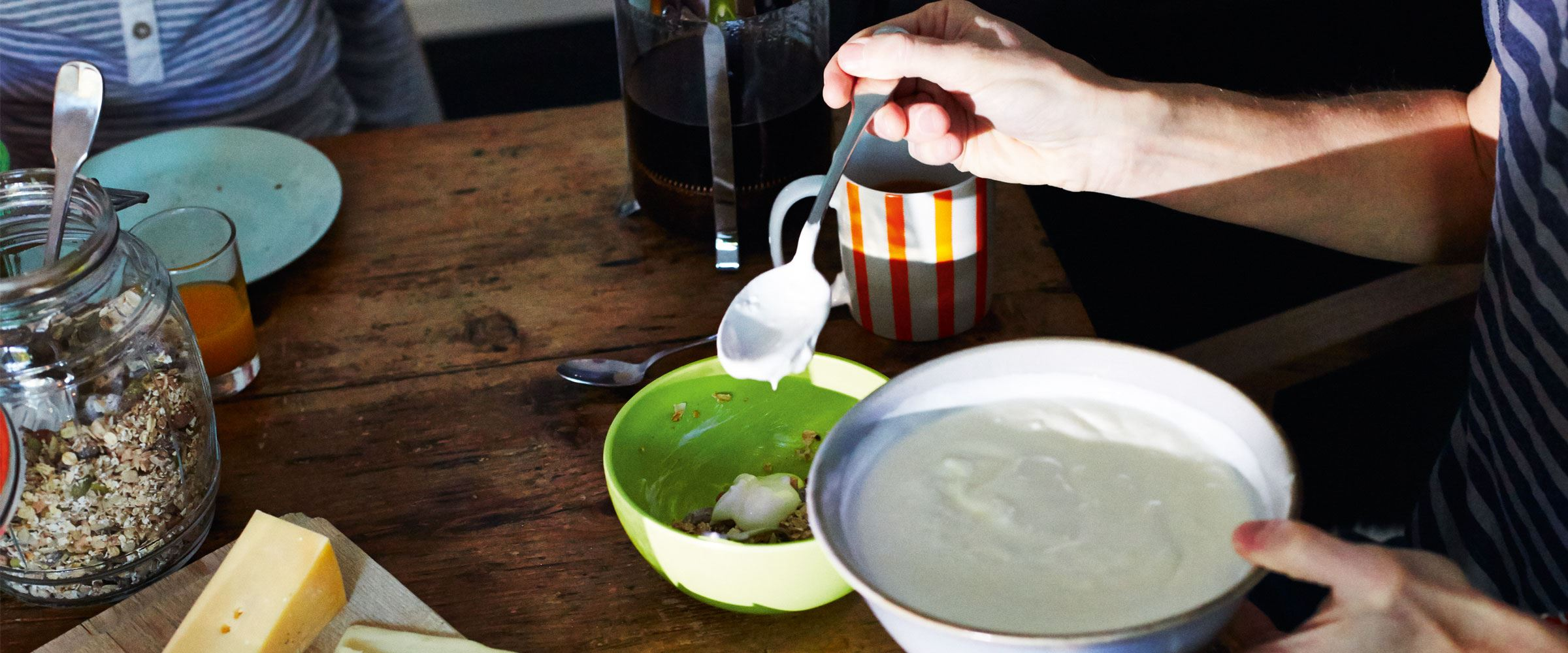 A person mixing yoghurt with grains in a bowl