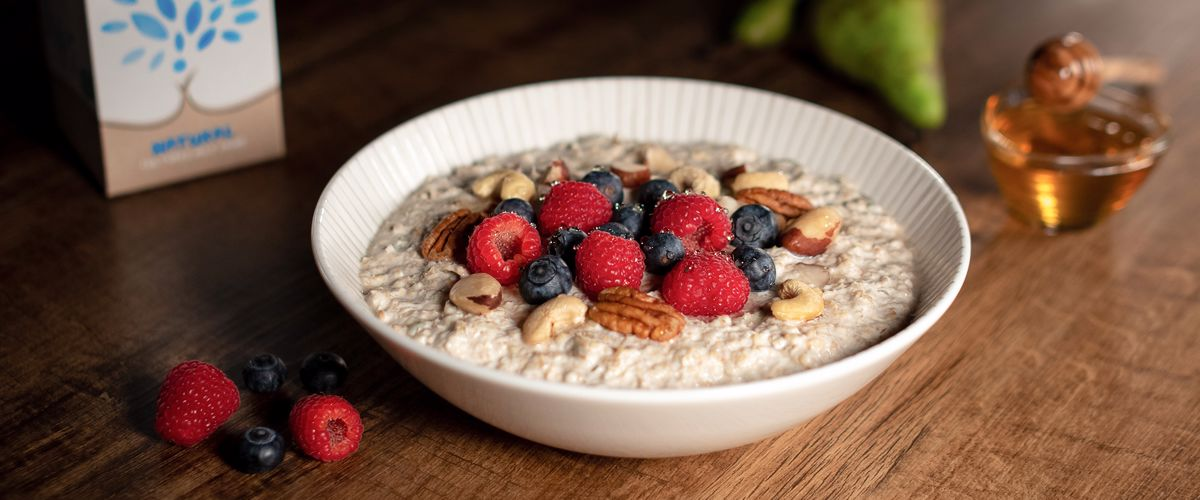A bowl of muesli topped with berries and nuts