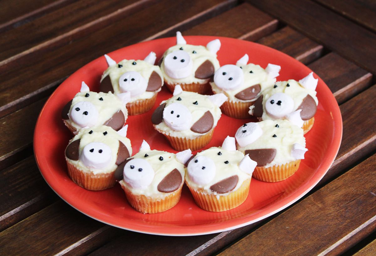 A plate of cupcakes with cow face icing