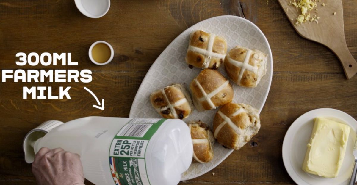Hot Cross Buns next to a hand pouring farmers milk into a jug. 300ml Farmers Milk