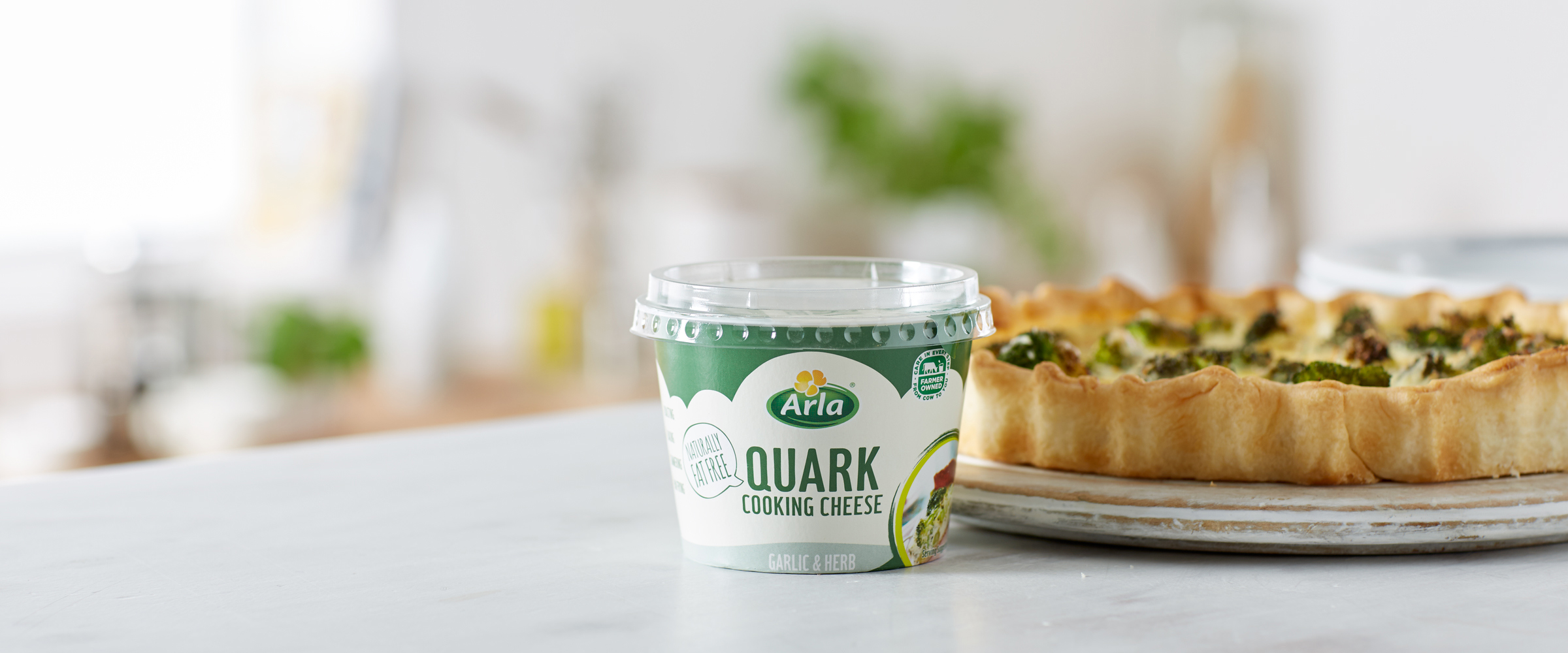 A tub of Arla Quark Garlic & Herb in front of a broccoli quiche