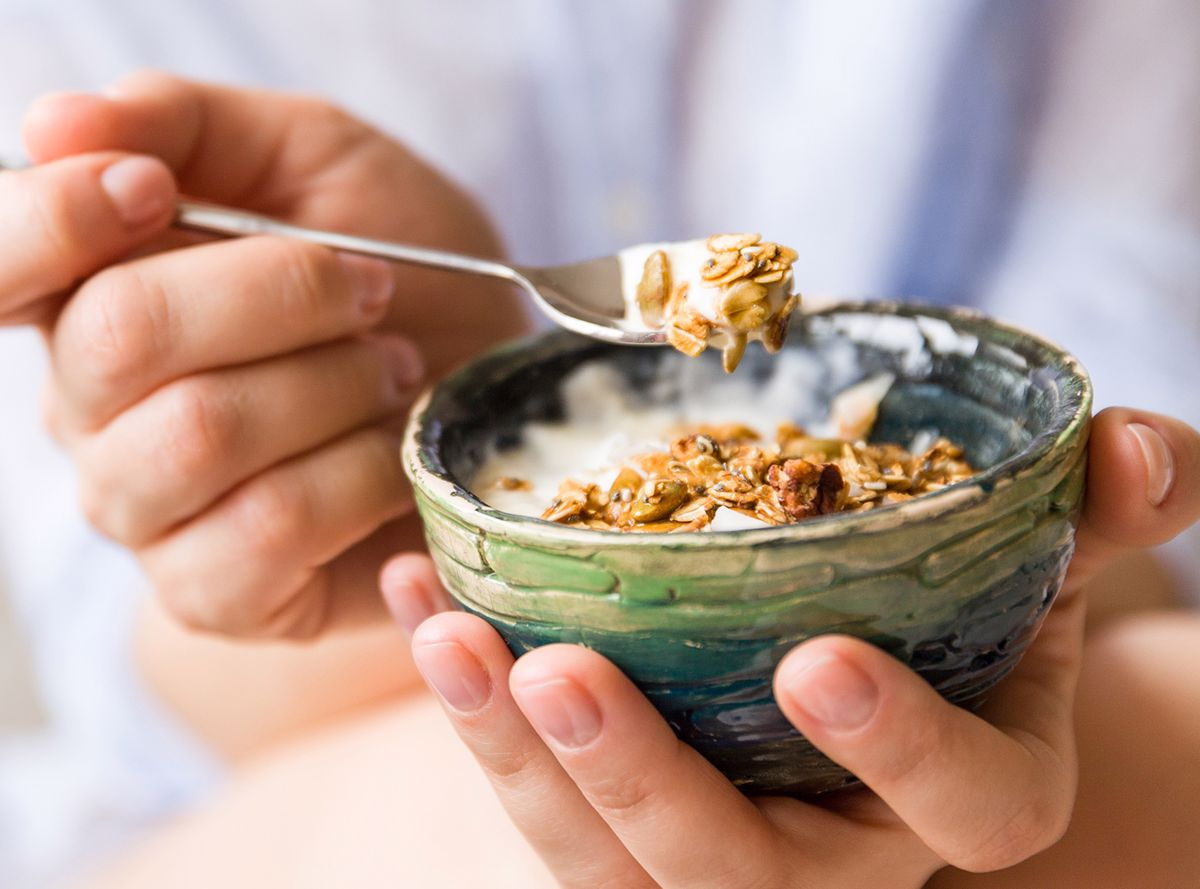 Yogurt and muesli spooned out of a bowl
