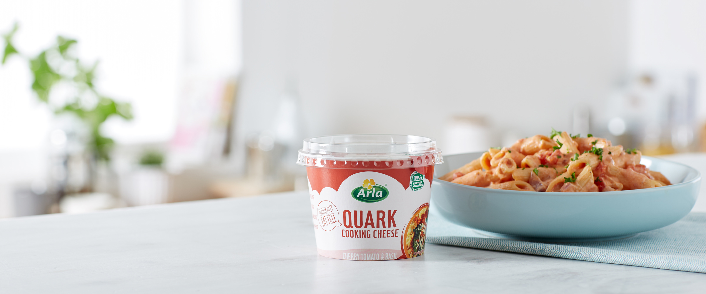 A tub of Arla Quark Cherry Tomato & Basil in front of a pasta dish