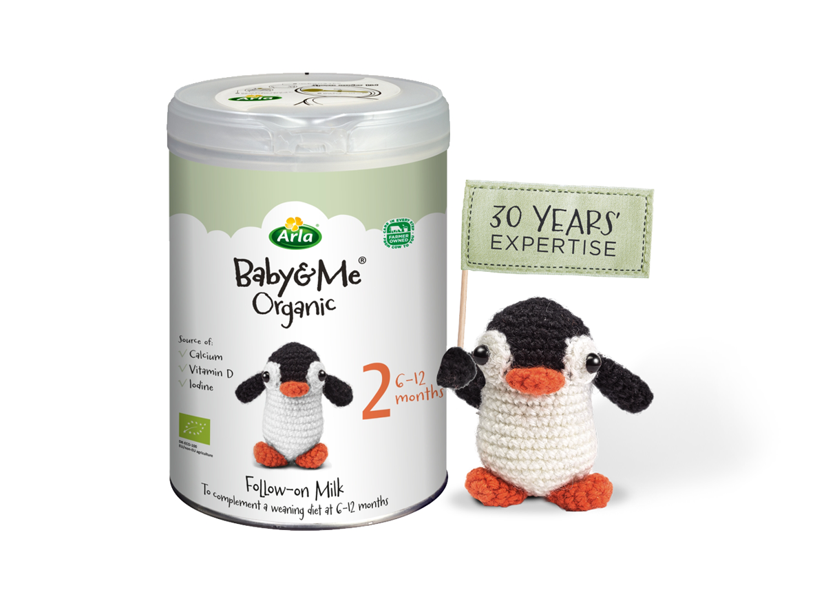 Arla Baby & Me Organic pack next to a knitted penguin toy holding a flag that says 30 years' expertise