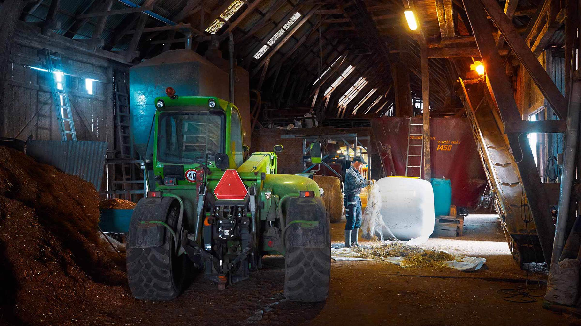 A farmer and his tractor in a barn
