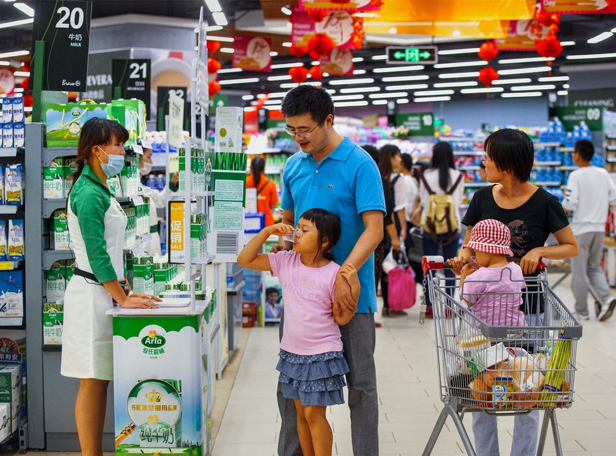A child sampling Arla milk with her family in a chinese supermarket