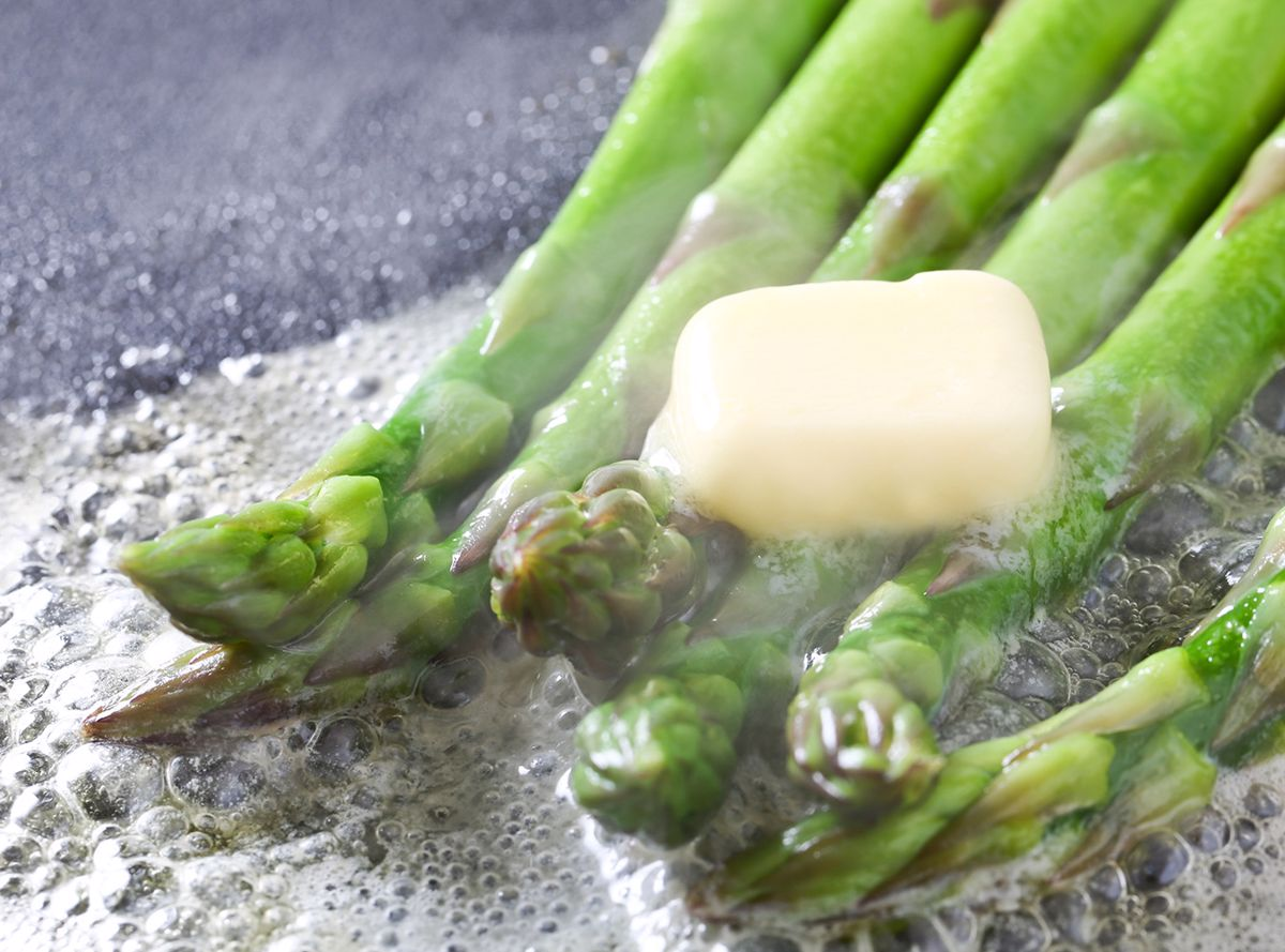 Butter melting onto cooking asparagus