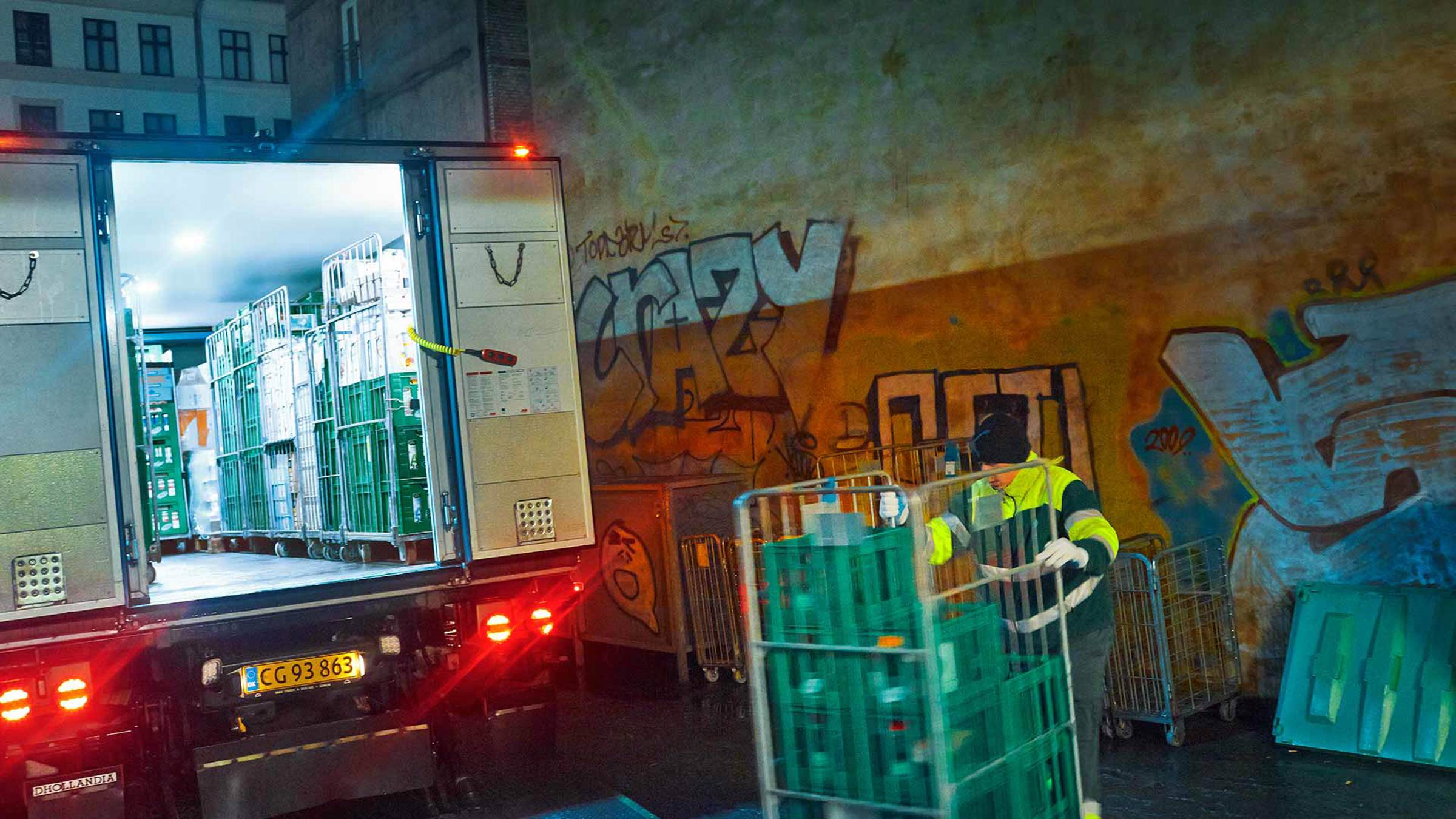 A worker loading trolleys into a truck at night
