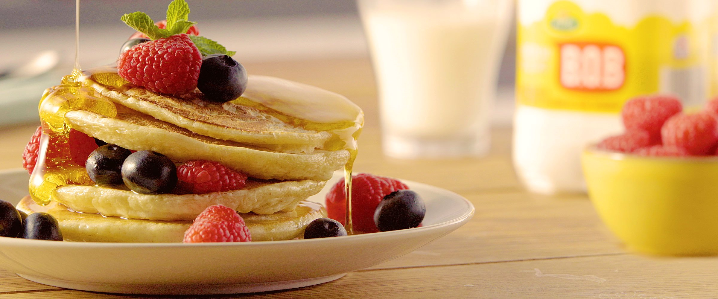 A stack of pancakes covered in honey and berries