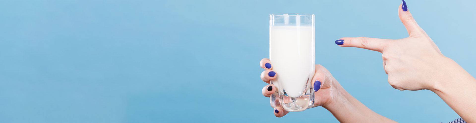 A pair of hands with purple painted nails with one hand pointing towards a glass of milk held in the other