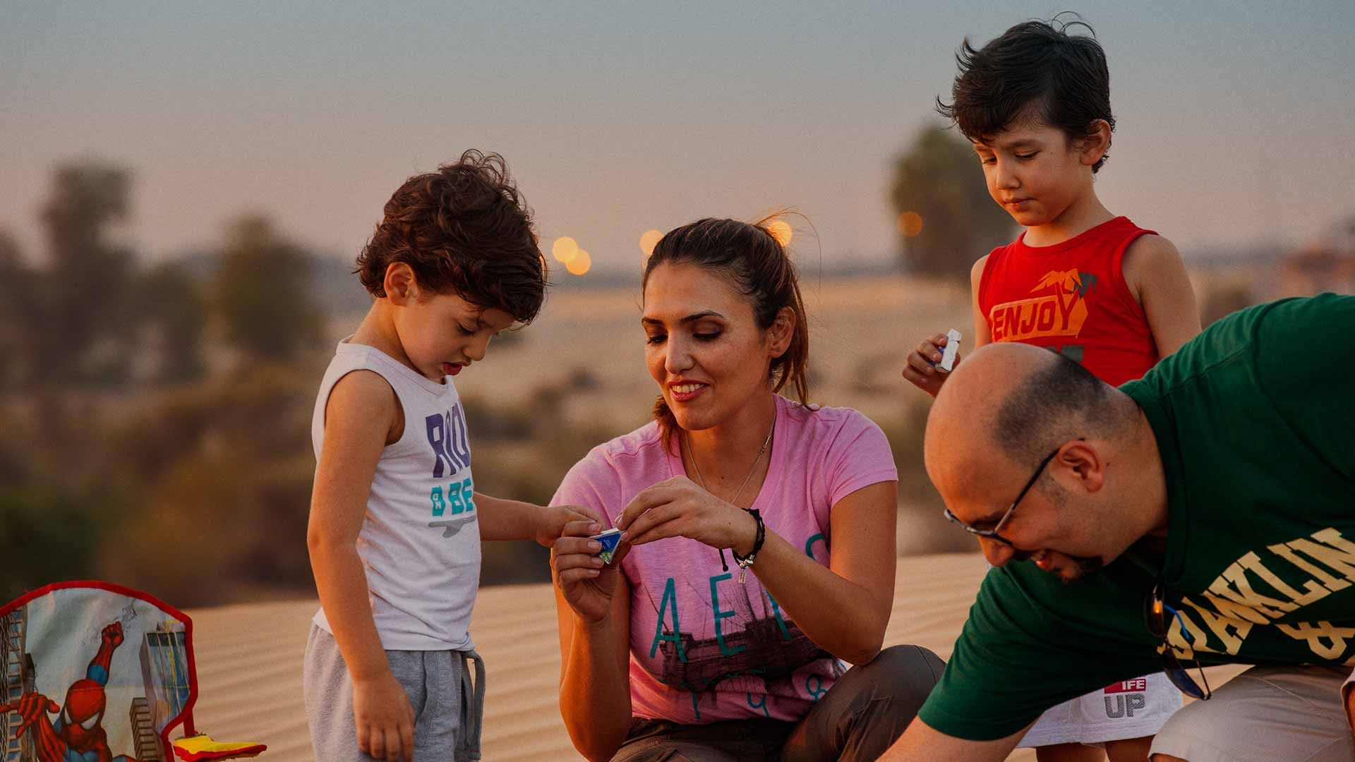 A family eating Arla cheese triangles in a desert