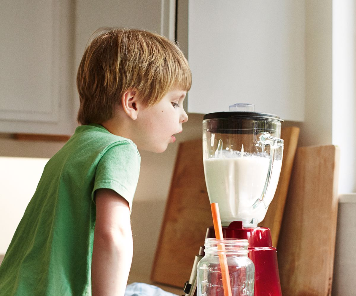 A young child watching a milk drink in a blender