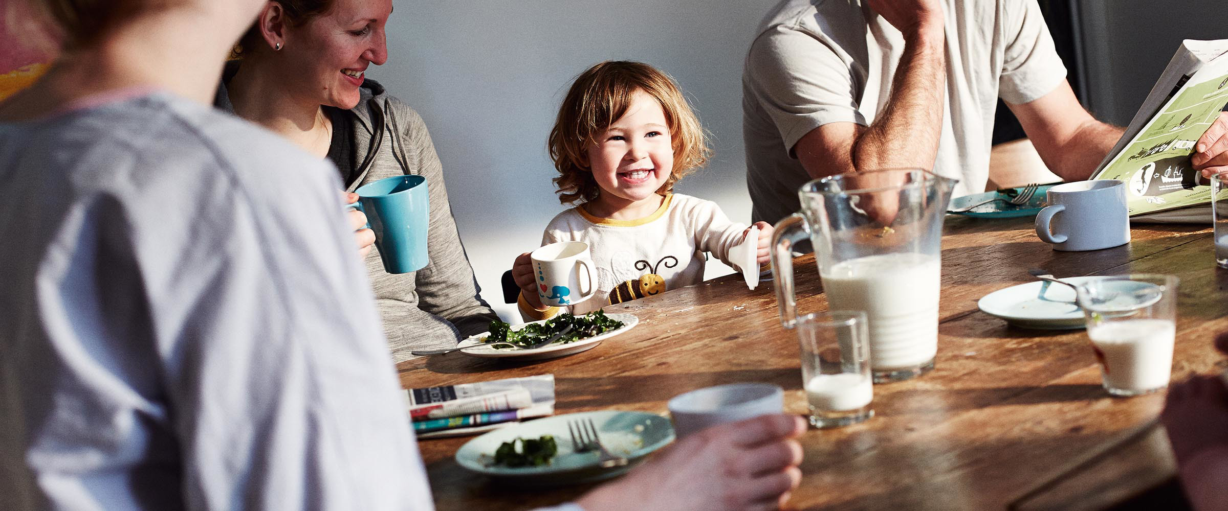A young child smiling at the dinner table with their family