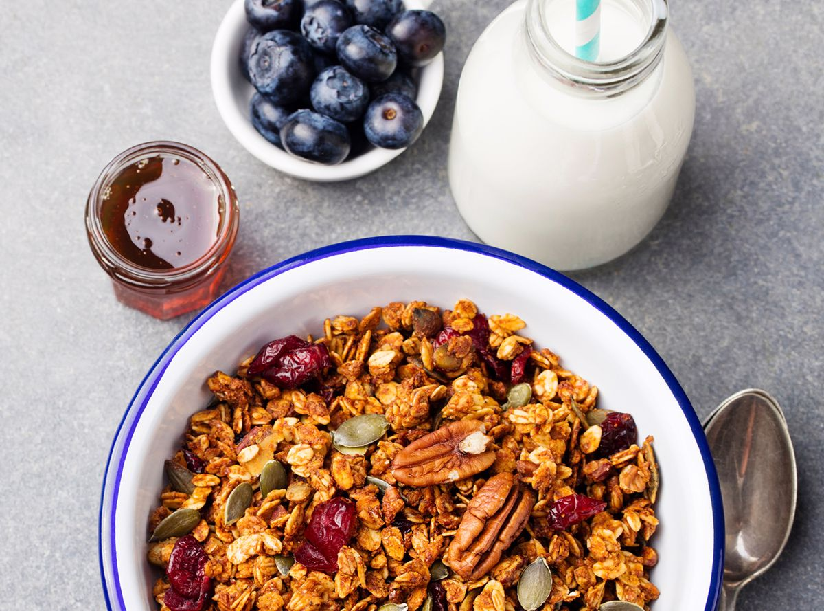 A bowl of oats with nuts, seeds and dried fruit next to blueberries, honey and milk
