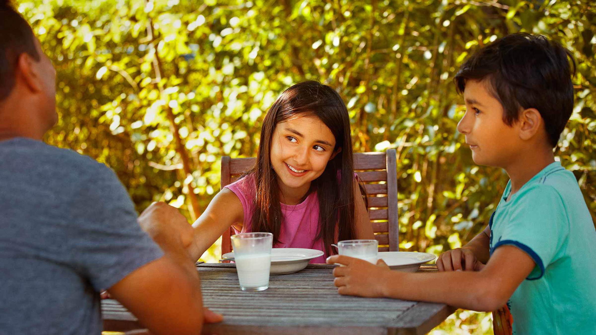 Children smiling at an outdoor dinner table