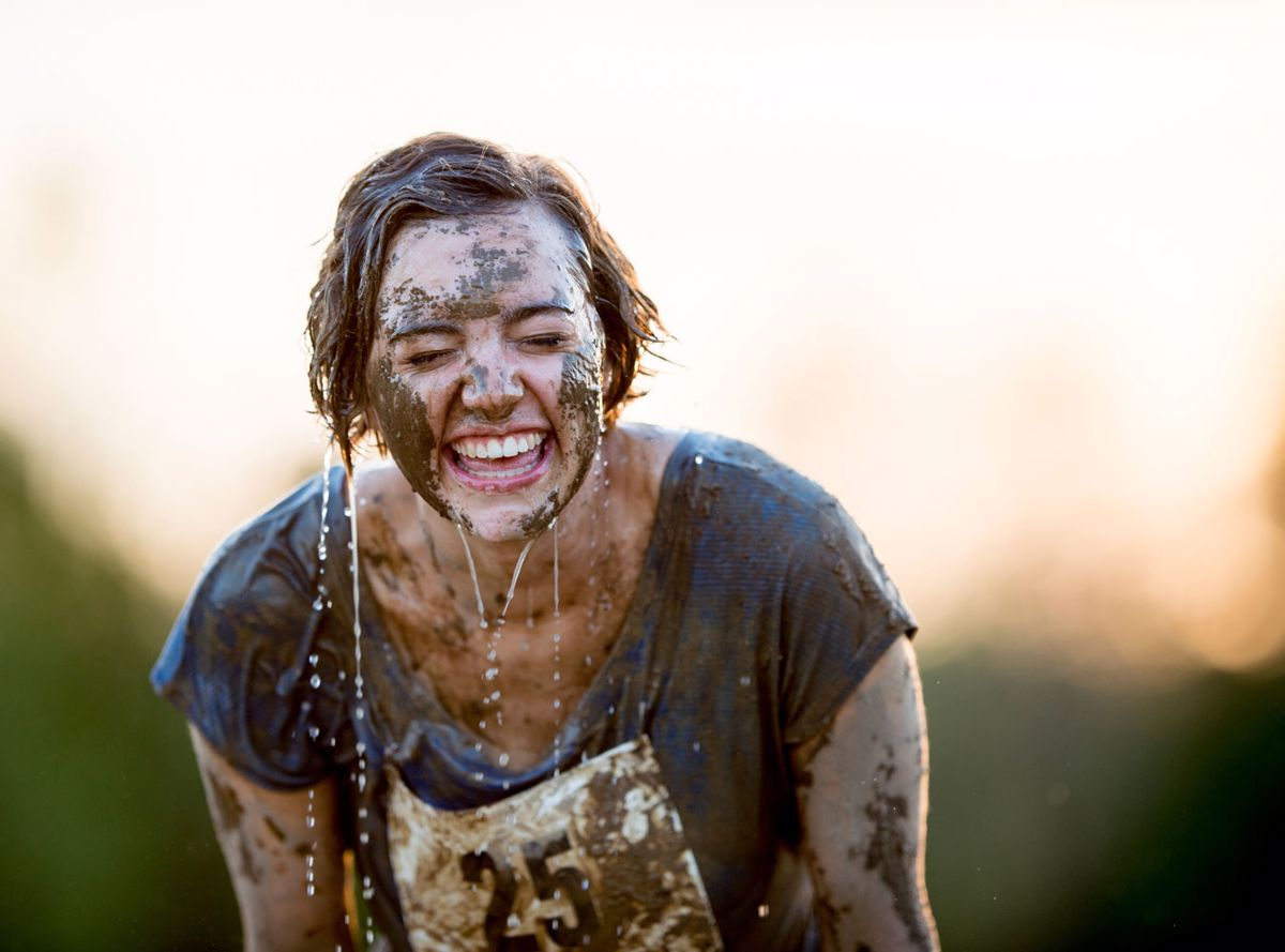 Female runner covered in mud and water smiling
