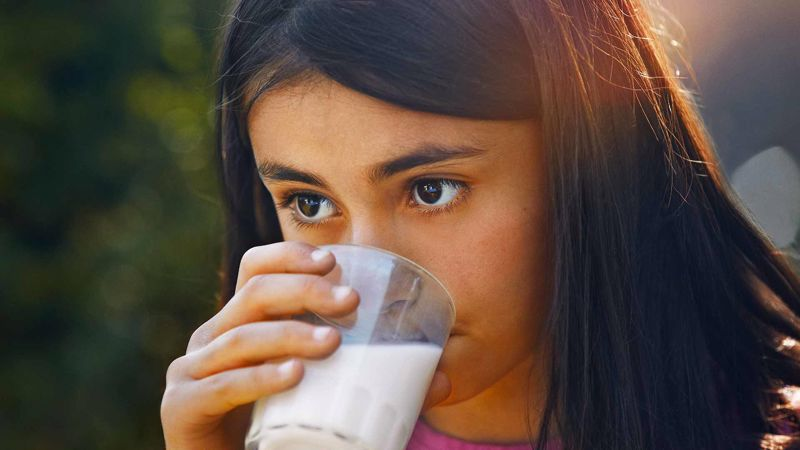 A girl drinking a glass of milk