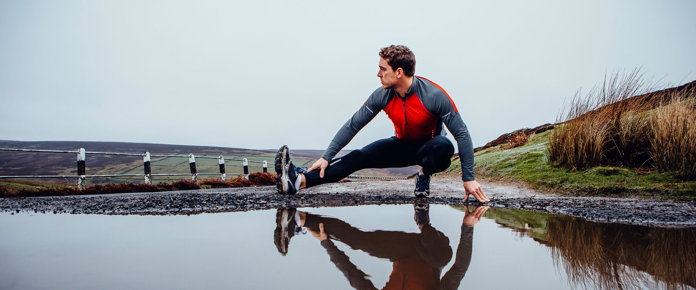 Male athlete on a country trail stretching in front of a puddle
