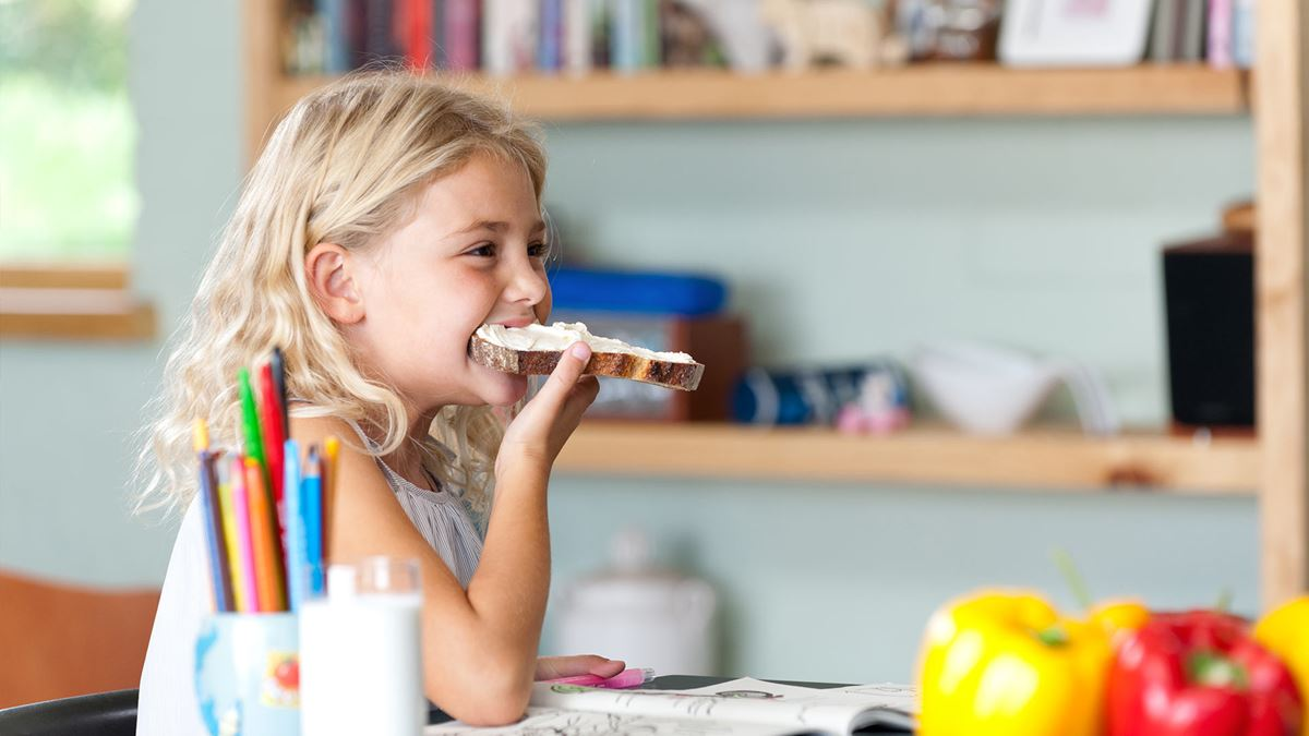 A girl eating a slice of bread with cream cheese