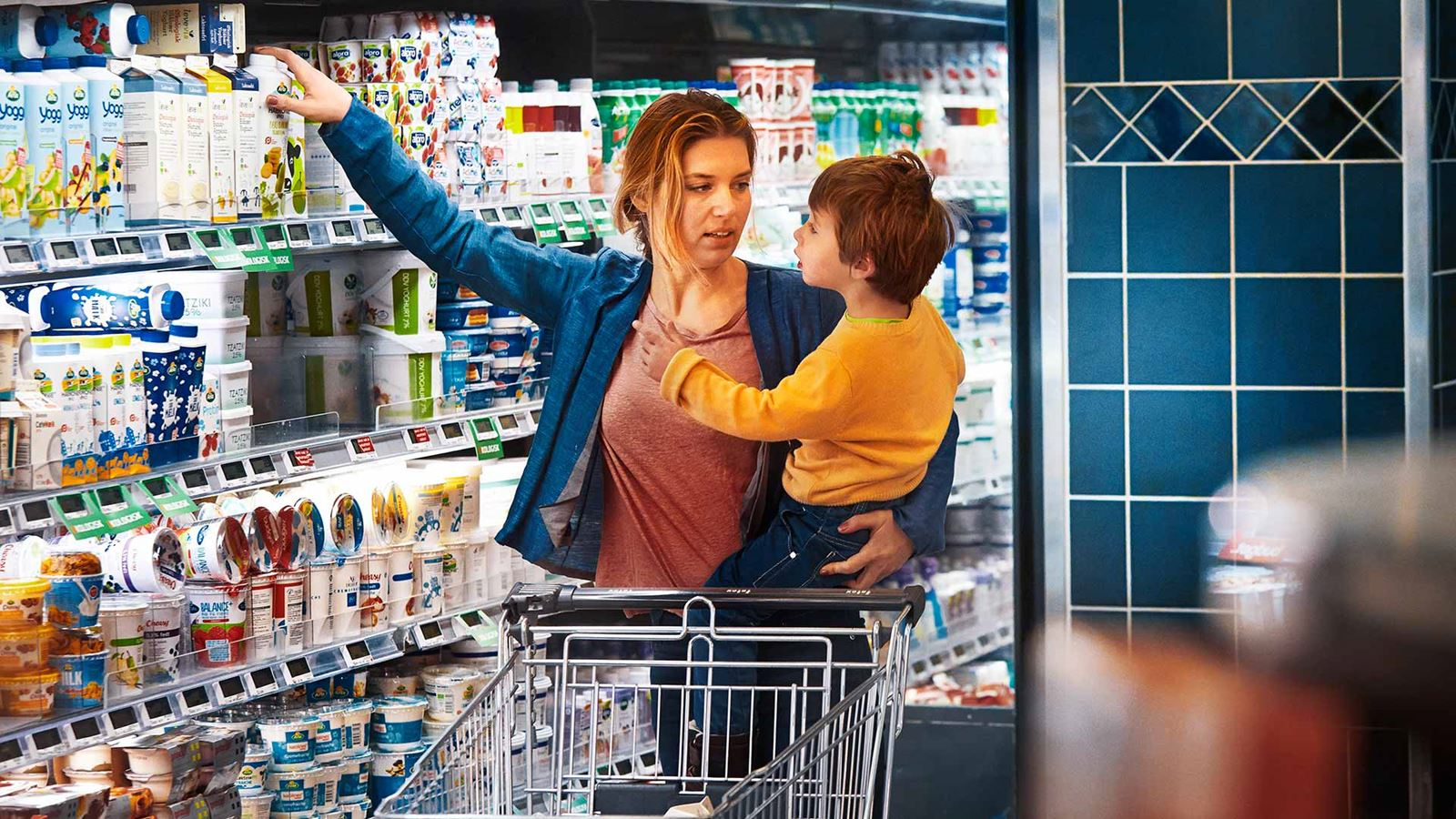 A mother holding her child and picking up a carton of Arla milk at a supermarket