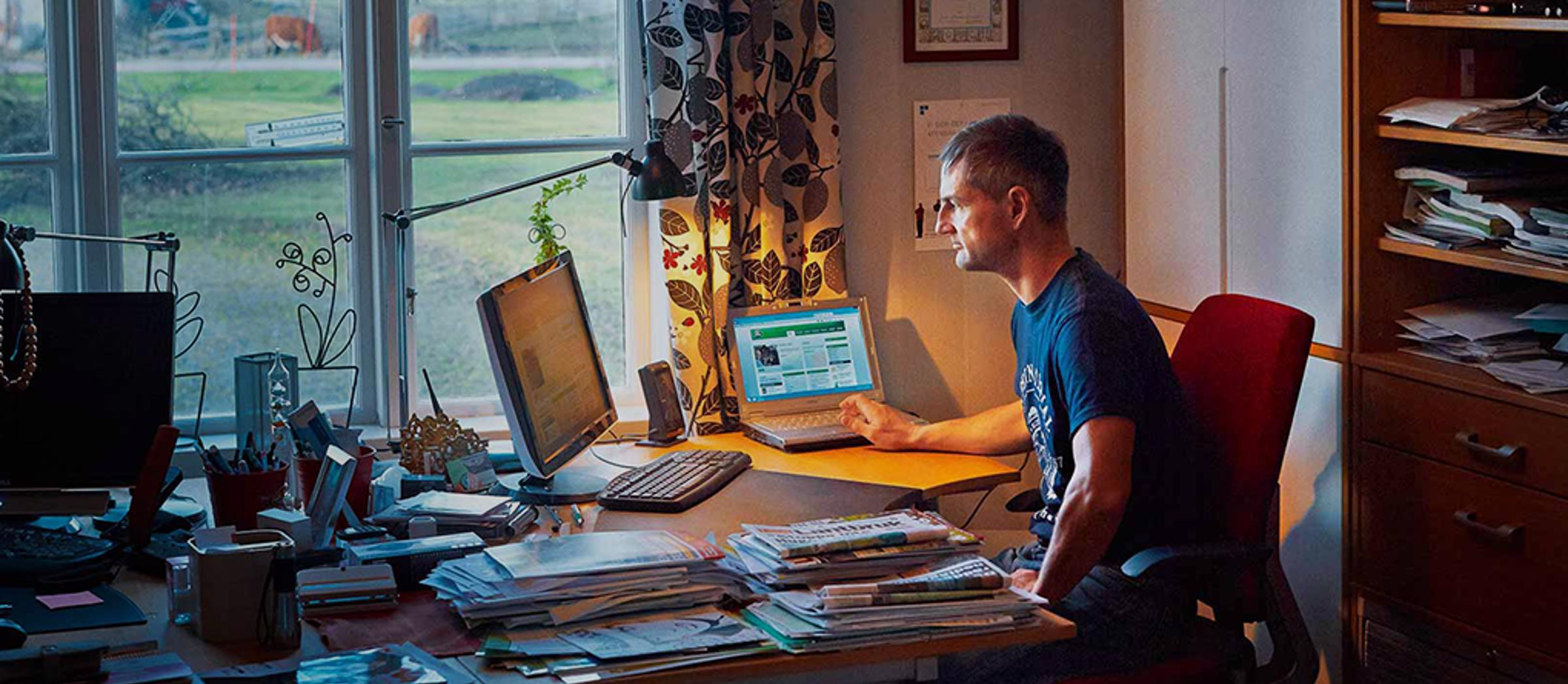 A farmer sat at a desk in his home office
