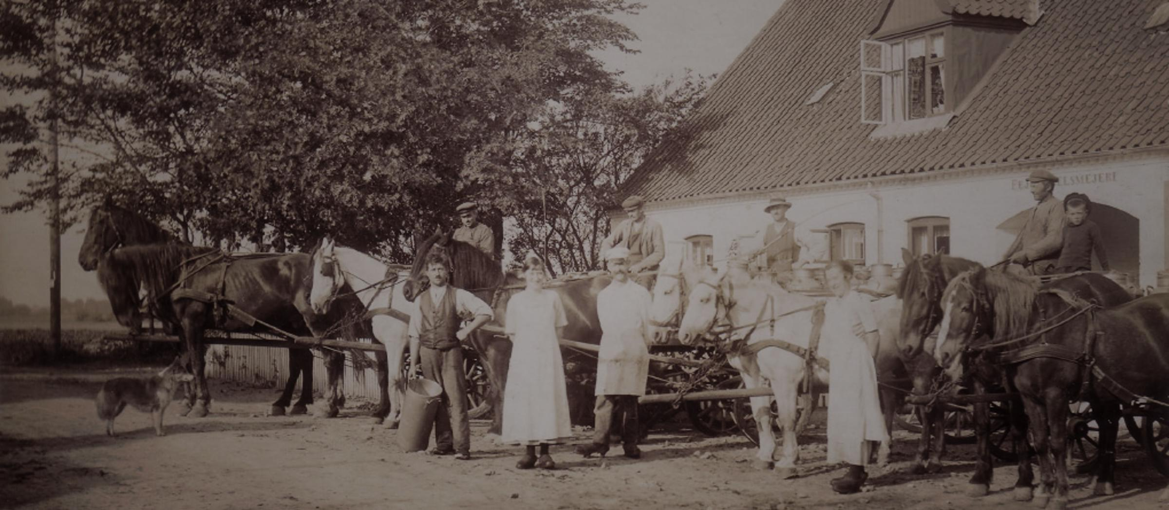 Old black and white image of farmers and horses with carriages