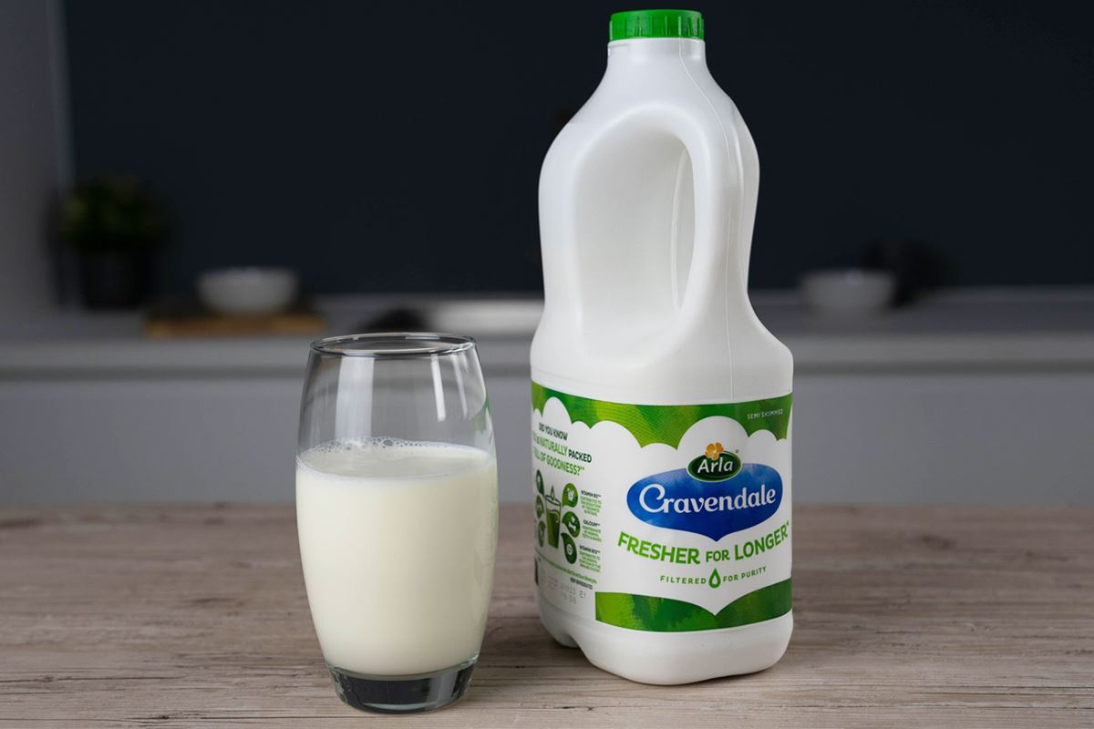 A glass of milk next to a bottle of Arla Cravendale