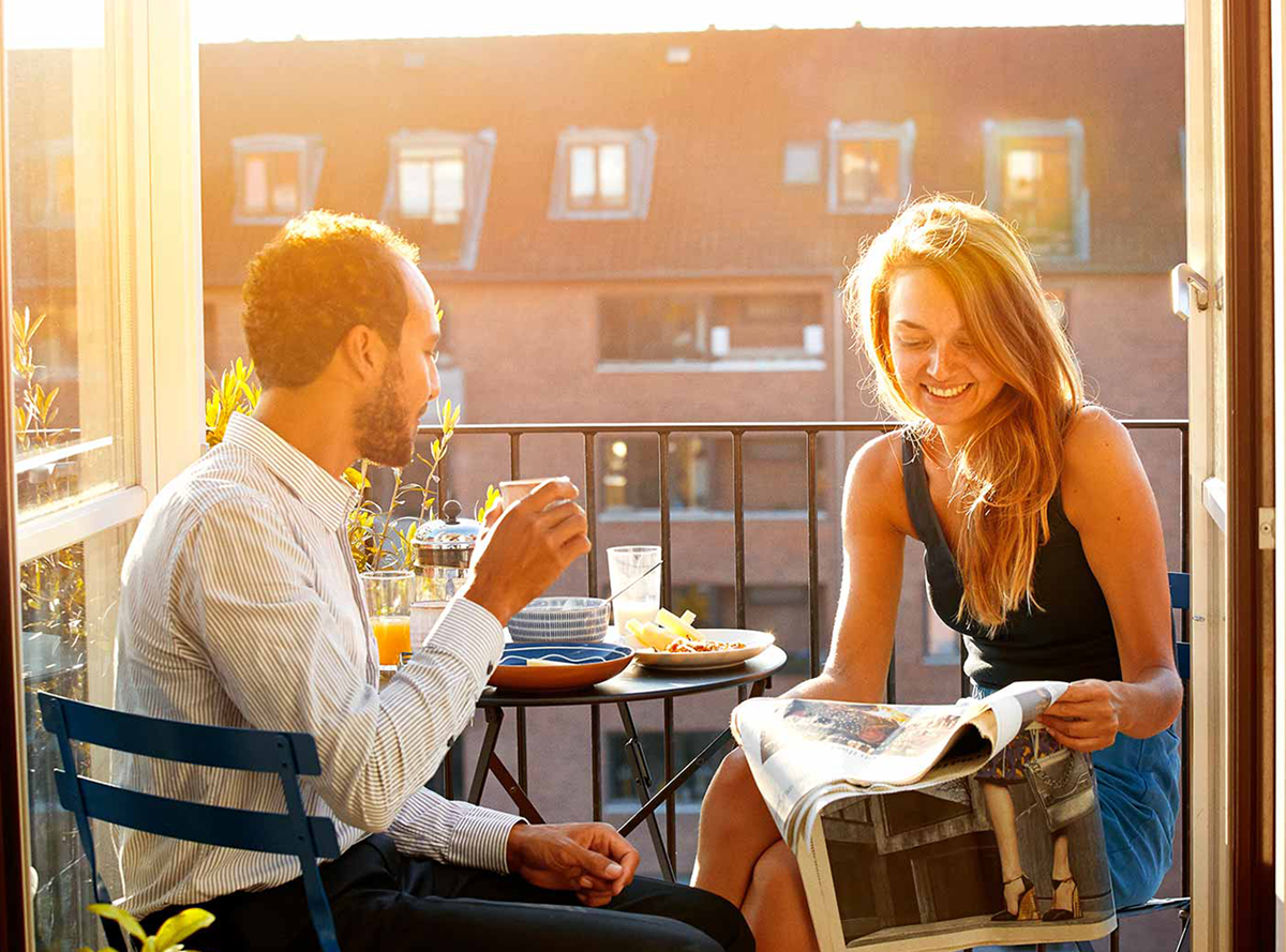A couple eating a meal on a balcony