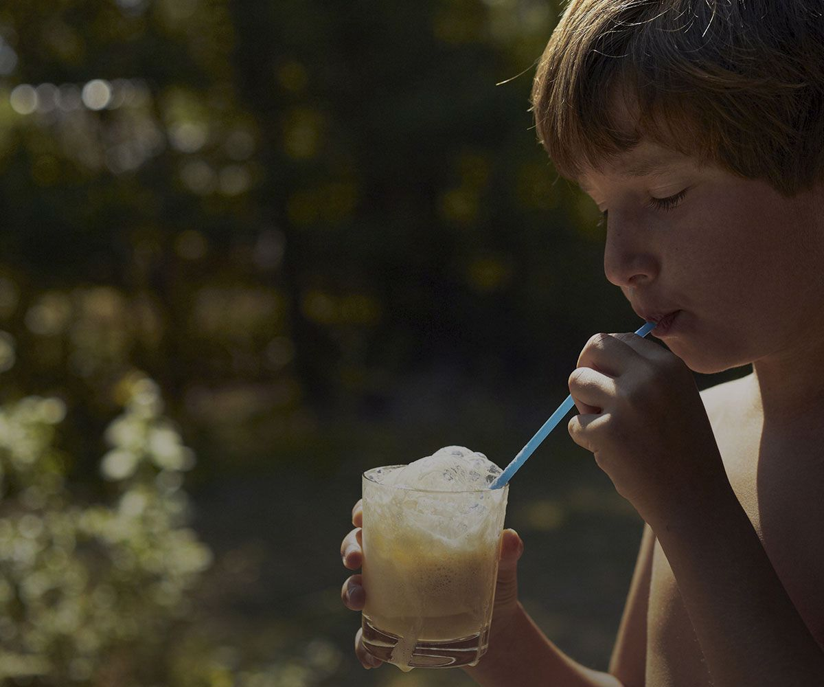 Boy drinking a milk drink outside
