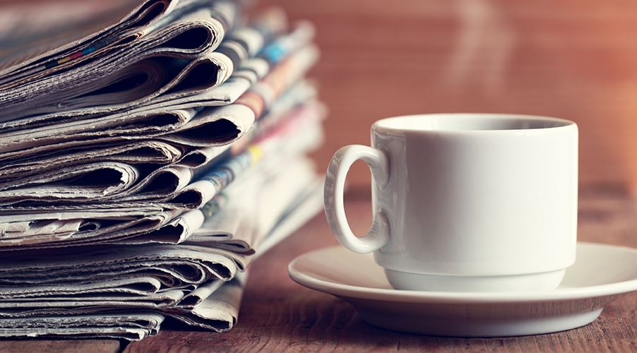 A steaming mug next to a stack of newspapers