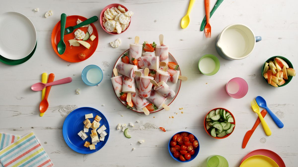 Strawberry ice lollies on a plate surrounded by bowls, cups, and cutlery