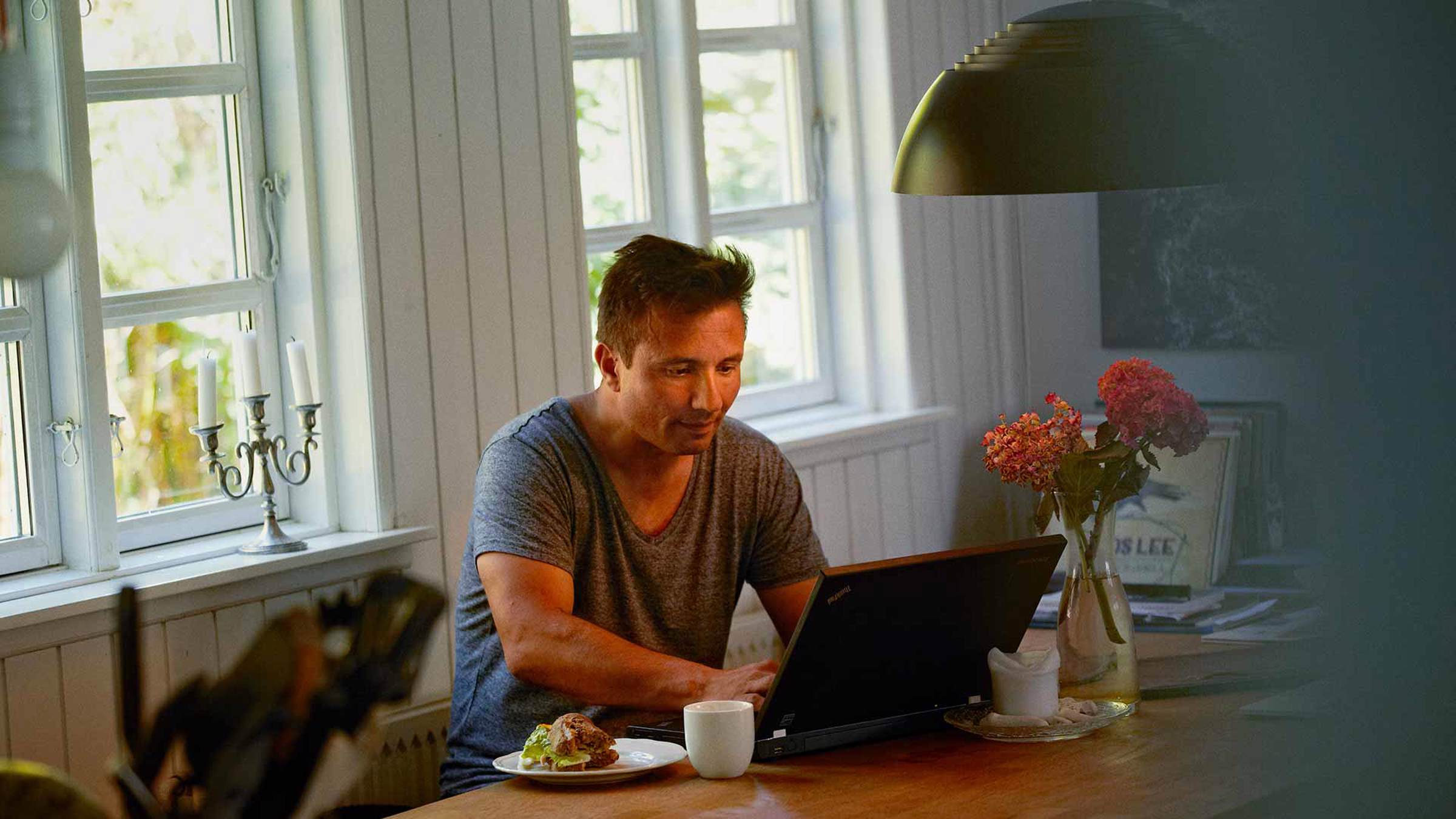 Man using a laptop with a sandwich and mug by his side