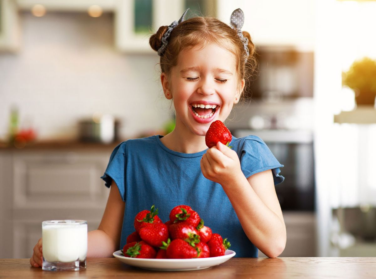 Girl laughing and eating strawberries