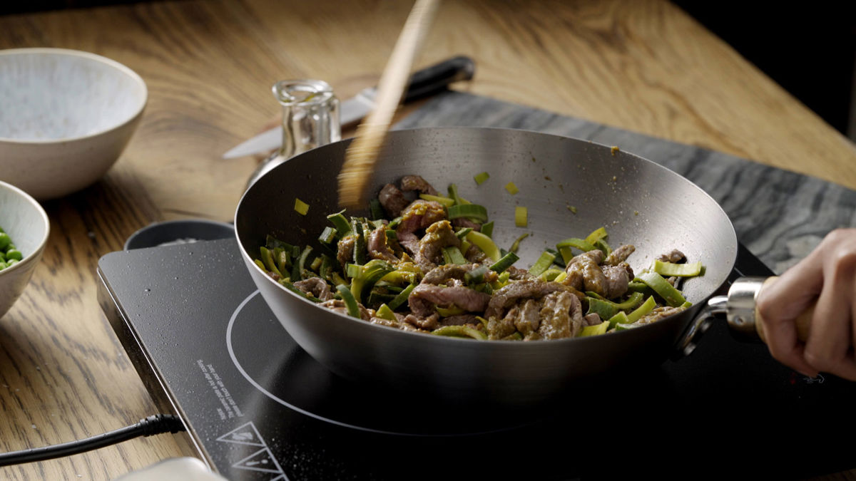 Beef and vegetables being stirred in a wok