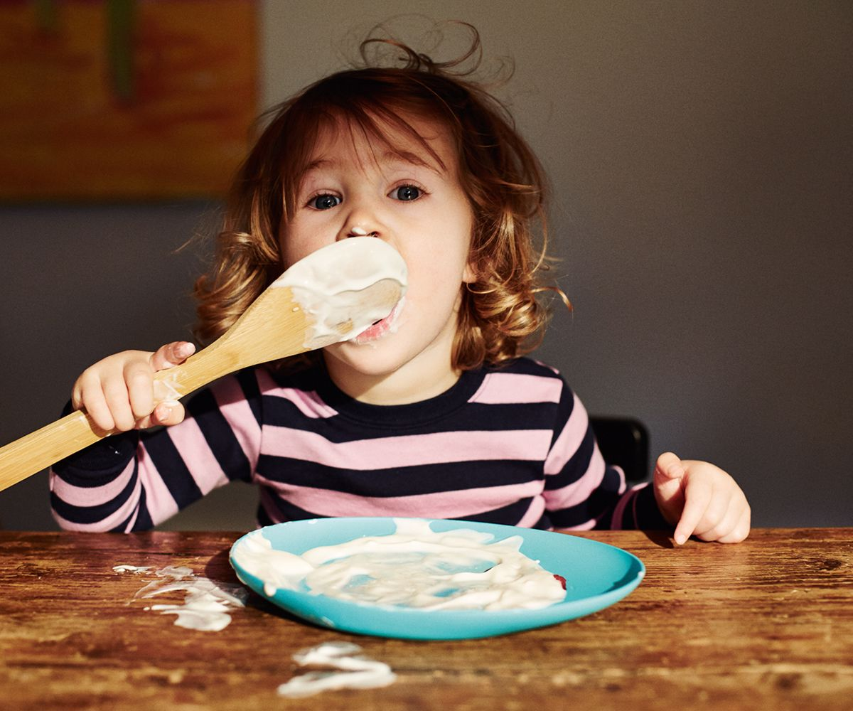 A young child licking yoghurt from a wooden spoon