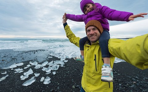 Child sitting on her dads shoulders in iceland