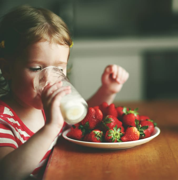 Image of child drinking milk with strawberries