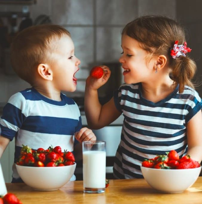 Image of two children eating strawberries